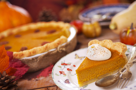 pumpkin pie: Homemade pumpkin pie on a rustic table with autumn decorations. Stock Photo