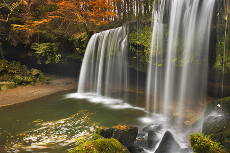 The Nabegataki Falls on the island of Kyushu, Japan surrounded by autumn colours. 免版税图像