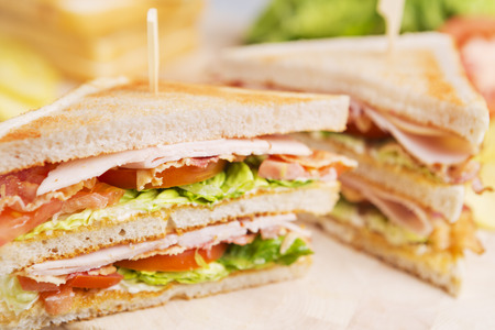 sandwich: A club sandwich on a rustic table in bright light. Stock Photo