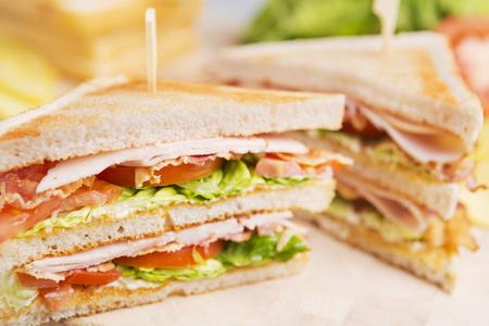 sandwich de pollo: Un s�ndwich club en una mesa r�stica con luz brillante.
