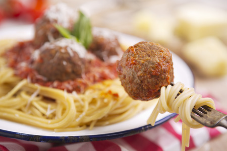 grated parmesan cheese: A plate with spaghetti with meatballs, topped with some grated parmesan cheese and basil. One meatball is picked up with a fork.