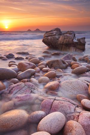 landschap: De prachtige rotsachtige strand van Porth Nanven in Cornwall, Engeland bij zonsondergang.