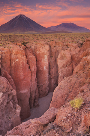 stratovolcano: A narrow canyon with a volcano in the distance. Photographed at the foot of Volcan Licancabur in the Atacama Desert, northern Chile, at sunset.