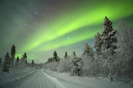 winter people: Spectacular aurora borealis northern lights on a track through winter landscape in Finnish Lapland. Stock Photo