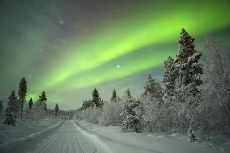 Spektakuläre Aurora borealis Nordlichter auf einer Spur durch Winterlandschaft im finnischen Lappland.