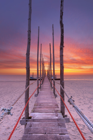 jetty: Spectacular sunrise colours over a jetty on a beach on the island of Texel in The Netherlands. Stock Photo