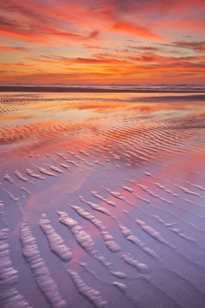 over the sea: Beautiful sunset and reflections on the beach at low tide.