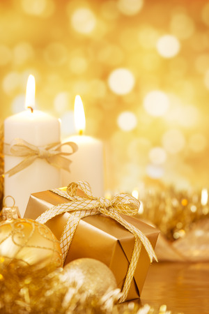 christmas candle: Gold Christmas baubles, candles and a gift on a bright glittering gold background. Stock Photo