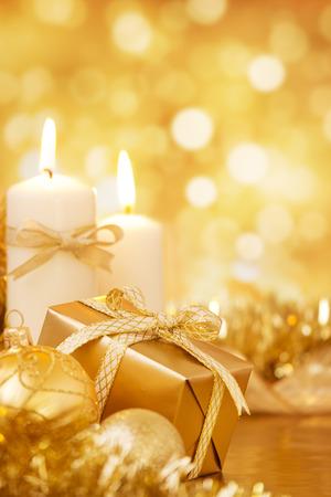 candela: Palline di Natale oro, candele e un dono su un luminoso sfondo scintillante dell'oro.