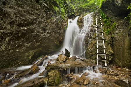 technically: A Technically aided trail along a waterfall in a lush gorge in Slovensky Raj in Slovakia.