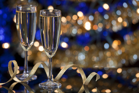 A New Year's Eve scene with champagne glasses and Christmas lights in the background.