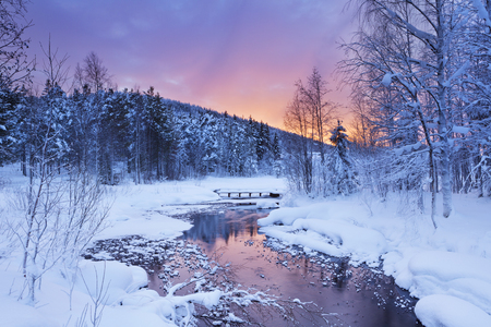 A frozen river in a wintry landscape. Photographed near Levi in Finnish Lapland at sunrise.