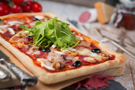 Homemade rectangular pepperoni pizza on a rustic table with ingredients. Stock Photo