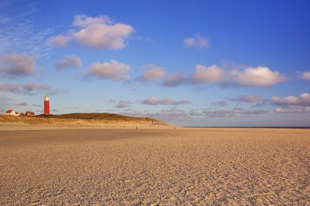 texel: The lighthouse of the island of Texel in The Netherlands in beautiful early morning sunlight. Photographed from the wide beach below. Stock Photo