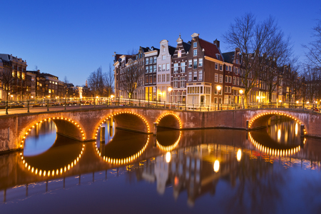 night life: Bridges over a crossroads of canals in the city of Amsterdam, The Netherlands at night.