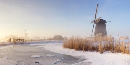 schermerhorn: Traditional Dutch windmills on a beautiful frosty and foggy morning.