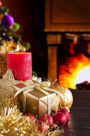 mantelpiece: Christmas decorations, a gift and a candle in front of a fireplace. A fire is burning in the fireplace and Christmas stockings are hanging on the mantelpiece. A Christmas tree is standing next to the fireplace in the background.