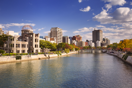 The Atomic Bomb Dome on the left and the Peace Memorial Park on the right along the river in Hiroshima on a sunny afternoon in autumn.