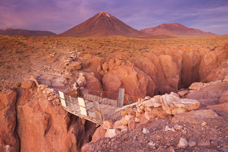 rickety: A rickety bridge over a narrow canyon with a volcano in the distance. Photographed at the foot of Volcan Licancabur in the Atacama Desert, northern Chile, at sunset.
