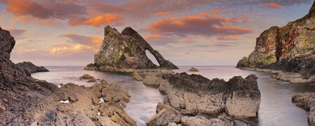 fiddle: The Bow Fiddle Rock along the Moray coast of Scotland, photographed at dusk. Stock Photo