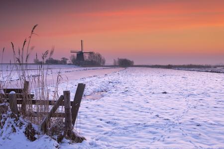 Tipico paesaggio polder olandese con un mulino a vento tradizionale. Fotografato in inverno all'alba.