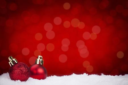 Deux petites boules de Noël rouges sur la neige avec des lumières rouges defocused en arrière-plan. Banque d'images