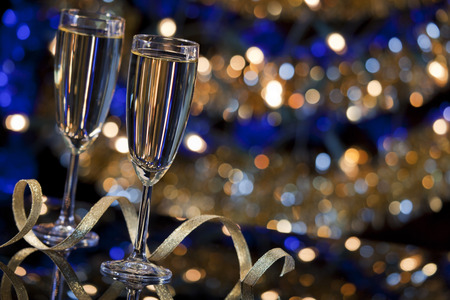 A New Years Eve scene with champagne glasses and Christmas lights in the background.
