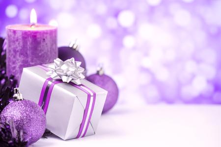 Babioles pourpres et d'argent de Noël, un cadeau et une bougie en face de lumières mauves et blanches défocalisées. Banque d'images