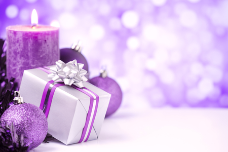 medium shot: Purple and silver Christmas baubles, a gift and a candle in front of defocused purple and white lights.