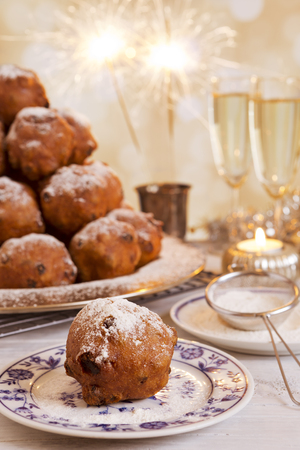 'Oliebollen', traditional Dutch pastry for New Year's Eve. With champagne and sparklers in the background. Reklamní fotografie - 47670161