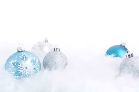 feathery: Blue and silver Christmas baubles on a soft feathery surface with a white background.