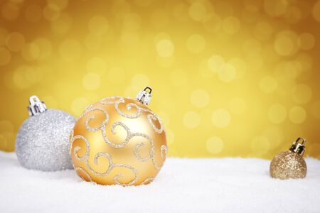 golden ball: Golden and silver Christmas baubles on snow with defocused golden lights in the background. Shallow depth of field.