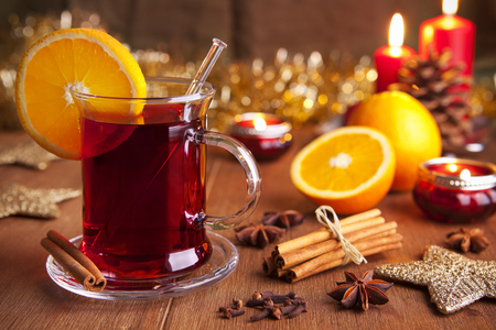 A glass with mulled wine or glühwein on a rustic table with ingredients and Christmas decorations. Reklamní fotografie - 47721004