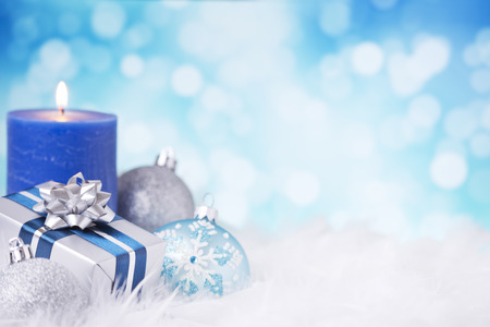 feathery: Blue and silver Christmas baubles, a gift and a candle on a soft feathery surface in front of defocused blue and white lights. Stock Photo