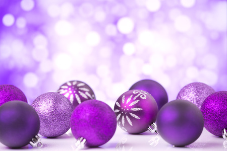 christmas baubles: Purple Christmas baubles in front of defocused purple and white lights.