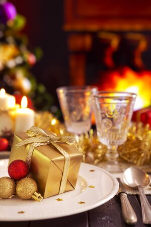 mantelpiece: A romantic Christmas dinner table setting with candles and Christmas decorations. A fire is burning in the fireplace and Christmas stockings are hanging on the mantelpiece. A Christmas tree is standing next to the fireplace in the background.