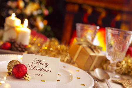 A romantic Christmas dinner table setting with candles and Christmas decorations. On the plate a note with the words 'Merry Christmas' is waiting for a guest. A fire is burning in the fireplace in the background. A Christmas tree is standing next to the f