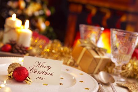 """velas de navidad: Una cena de Navidad ajuste de la tabla romántica con velas y decoraciones de Navidad. En la placa de una nota con las palabras """"Feliz Navidad"""" está a la espera de un huésped. Un fuego arde en la chimenea en el fondo. Un árbol de Navidad está de pie al lado de la f Foto de archivo"""
