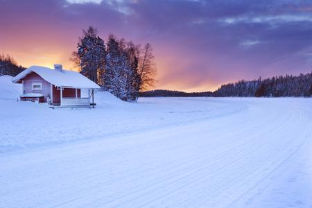 casa de campo: Una pequeña casa de campo en el borde de un lago congelado. Fotografiado cerca de Levi en la Laponia finlandesa al amanecer.