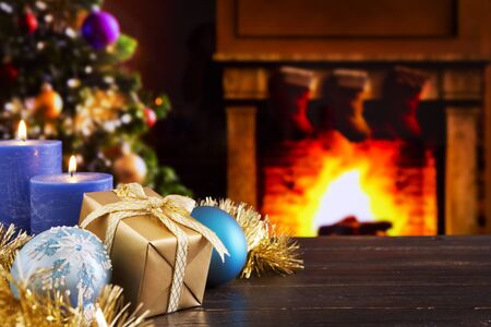 christmas tree presents: Christmas decorations, a gift and candles in front of a fireplace. A fire is burning in the fireplace and Christmas stockings are hanging on the mantelpiece. A Christmas tree is standing next to the fireplace in the background. Stock Photo