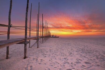 Spectacular sunrise colours over a jetty on a beach on the island of Texel in The Netherlands. Reklamní fotografie