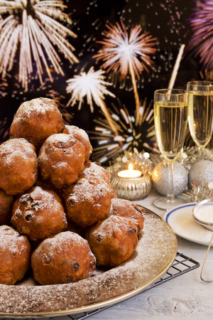 dutch culture: Oliebollen, traditional Dutch pastry for New Years Eve. With champagne and fireworks in the background. Stock Photo