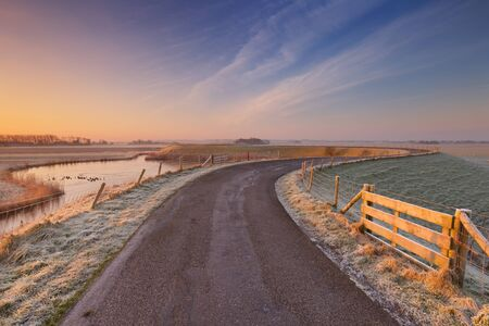 dyke: Typical Dutch landscape on a frosty morning at sunrise. This is part of the West-Frisian Circular Dyke, a dyke system that has been protecting a large region in the northwest of The Netherlands since the 13th century. Stock Photo