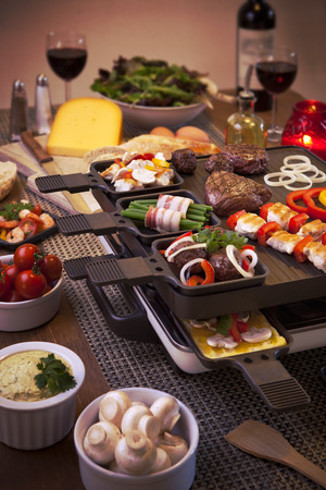 Swiss raclette or the Dutch variant 'gourmetten'. A table filled with ingredients for a dish that is usually served on celebratory evenings like Christmas or New Years Eve in The Netherlands. Stock Photo