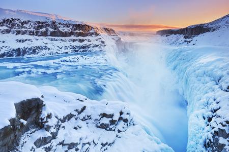 De Gullfoss Falls in IJsland in de winter, wanneer de watervallen zijn gedeeltelijk bevroren. Gefotografeerd bij zonsondergang. Stockfoto