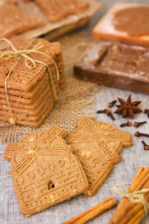 dutch culture: Traditional Dutch speculaas (spiced shortcrust cookies). With authentic wooden cookie cutters especially made for these cookies in the background. Stock Photo