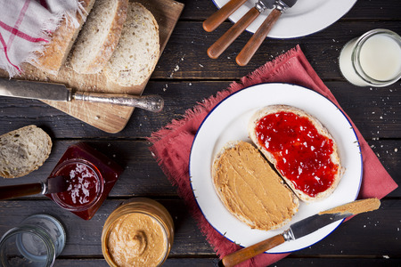 peanut butter and jelly sandwich: Peanut butter and jelly sandwich on a rustic table. Photographed from directly above.