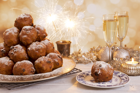 pastries: Oliebollen, traditional Dutch pastry for New Years Eve. With champagne and sparklers in the background. Stock Photo