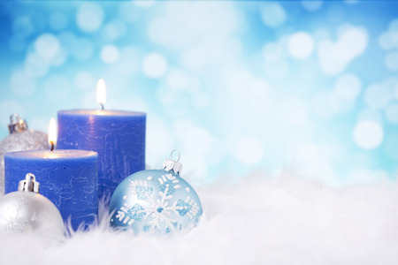candle lights: Blue and silver Christmas baubles and candles on a soft feathery surface in front of defocused blue and white lights.