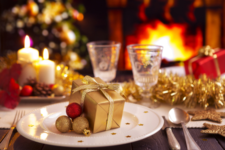 A romantic Christmas dinner table setting with candles and Christmas decorations. A fire is burning in the fireplace and Christmas stockings are hanging on the mantelpiece. A Christmas tree is standing next to the fireplace in the background. Reklamní fotografie - 49154495
